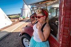 Blonde female poses near an abandoned classic car, wearing pin-up style hair and clothing stock image