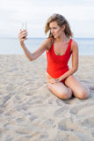 Blonde female in red bikini photographing herself on mobile phone Stock Image