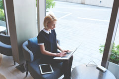 Blonde female restaurant owner is using portable net-book during work day Royalty Free Stock Photography
