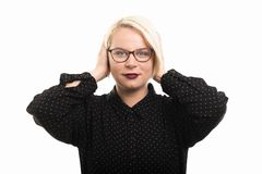 Blonde female teacher wearing glasses covering ears like deaf ge. Portrait of young blonde female teacher wearing glasses covering ears like deaf gesture royalty free stock image