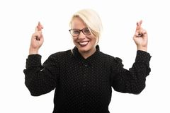Blonde female teacher wearing glasses showing double cross finge royalty free stock image