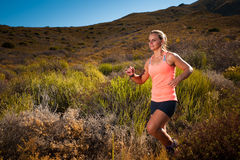 Blonde female trail runner running through a mountain landscape Royalty Free Stock Photo