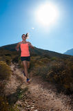 Blonde female trail runner running through a mountain landscape Royalty Free Stock Photos