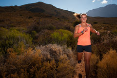 Blonde female trail runner running through a mountain landscape Royalty Free Stock Images