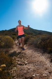 Blonde female trail runner running through a mountain landscape Stock Images
