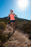 Blonde female trail runner running through a mountain landscape Royalty Free Stock Image