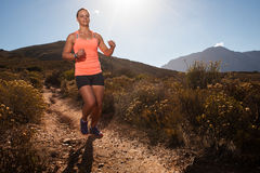 Blonde female trail runner running through a mountain landscape Stock Photos