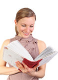 Blonde female watching her photo album. Young blonde female holding a book or photo album and smiling (isolated on white Stock Images