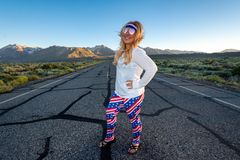 Blonde female wearing patriotic American clothing costume stands in the middle of a mountain road, concept for freedom and travel. Photo taken in Mammoth Lakes stock photography