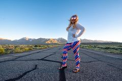 Blonde female wearing patriotic American clothing costume stands in the middle of a mountain road, concept for freedom and travel. Photo taken in Mammoth Lakes royalty free stock photo