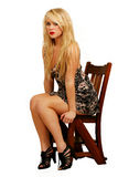 Blonde female in wooden chair. Pretty blonde female sitting or waiting in vintage wooden chair Royalty Free Stock Images