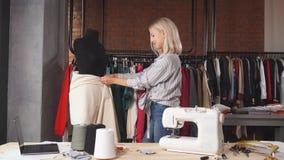 Blonde femalen designer measuring fabric on black dummy at work. Lifestyle, free time stock footage