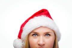 Blonde festivo que mira para arriba en el sombrero de santa Foto de archivo libre de regalías