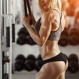 Blonde fitness girl. Classic bodybuilding. Muscular blonde woman doing exercises in the gym Royalty Free Stock Photos