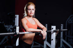 Blonde fitness girl with perfect shape body rests after sport workout in gym leaning on barbell Royalty Free Stock Photos