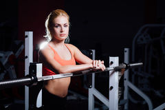 Blonde fitness girl with perfect shape body rests after sport workout in gym leaning on barbell. Blonde fitness girl with perfect shape body rests after sport Stock Photography