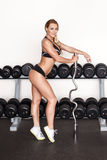 Blonde fitness woman posing with olympic bar Royalty Free Stock Photo
