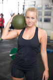 Blonde fitness woman with slam ball. Attractive young girl rests with a slam ball on the shoulder after workout at a fitness gym center. People workout in the Stock Images
