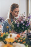 Blonde florist holding beautiful bouquet of flowers while working in flower shop Stock Photo