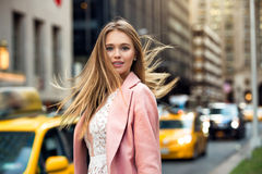 Blonde with flyaway hair in the background of New York City street with taxi cabs. Portrait of the blonde with flyaway hair in the background of New York City stock photo