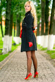 Blonde on footpath in park. Beautiful young woman in coat and red gloves has looked back in park Stock Photo