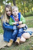 A blonde four-year-old boy in a green jacket looks surprised int royalty free stock photo