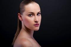 Blonde Frau über lächelnden blauen Augen des dunklen Hintergrundes Stockbilder