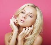 Blonde Frau über rosa Hintergrund Stockbild