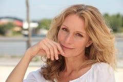 Blonde Frau auf Bank Stockfotos