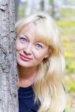 Blonde Frau auf Baumhintergrund Stockfotos