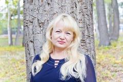 Blonde Frau auf Baumhintergrund Lizenzfreie Stockfotografie