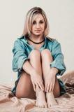 Blonde Frau auf Bett Stockfoto