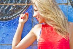 Blonde Frau auf blauer Wand Stockfoto
