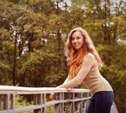 Blonde Frau auf Brücke im Herbstpark Stockfotos