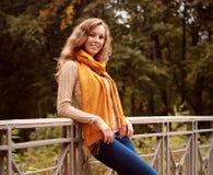 Blonde Frau auf Brücke im Herbstpark Lizenzfreies Stockfoto