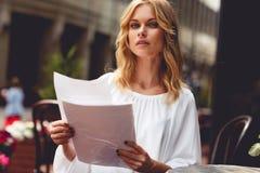 Blonde Frau auf Bruch Café- und haltenpapieren an den im Freien Lizenzfreie Stockbilder