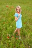 Blonde Frau auf dem Mohnblumegebiet Lizenzfreie Stockfotografie