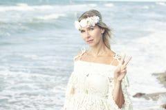 Blonde Frau auf dem Strand, der das Friedenszeichen macht Stockfotografie