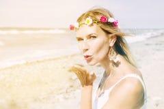 Blonde Frau auf dem Strand, der einen Kuss durchbrennt Stockbild