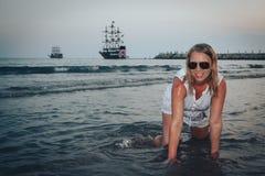 Blonde Frau auf dem Strand in einem Wasser des Meeres Stockbild
