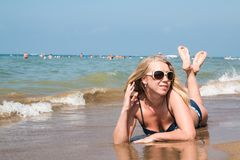 Blonde Frau auf dem Strand in einem Wasser des Meeres Lizenzfreies Stockbild