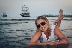 Blonde Frau auf dem Strand in einem Wasser des Meeres Stockfotos