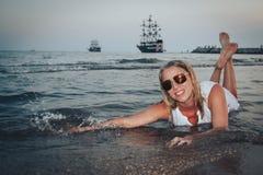 Blonde Frau auf dem Strand in einem Wasser des Meeres Lizenzfreies Stockfoto