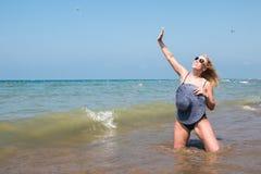 Blonde Frau auf dem Strand in einem Wasser des Meeres Stockfoto