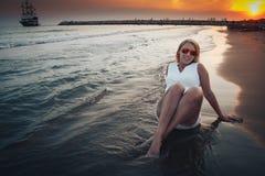 Blonde Frau auf dem Strand nahe Meer am Abend Lizenzfreie Stockbilder
