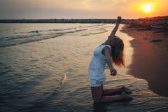 Blonde Frau auf dem Strand nahe Meer am Abend Lizenzfreie Stockfotografie