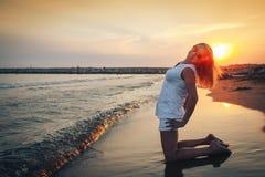Blonde Frau auf dem Strand nahe Meer am Abend Stockbilder