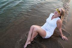 Blonde Frau auf dem Strand nahe Meer am Abend Stockfotografie