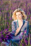 Blonde Frau auf dem violetten Gebiet Lizenzfreies Stockbild