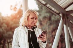 Blonde Frau auf der Brücke unter Verwendung des Smartphone Stockbild